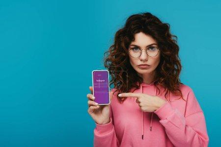 Photo pour Fille rousse bouclée attirante pointant avec le doigt au smartphone avec l'application d'Instagram sur l'écran d'isolement sur le bleu - image libre de droit