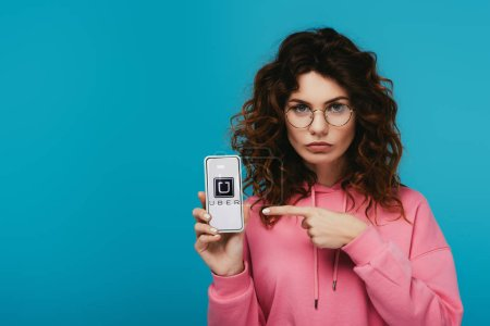 Photo pour Fille rousse bouclée attrayante pointant avec le doigt au smartphone avec l'application d'uber sur l'écran d'isolement sur le bleu - image libre de droit