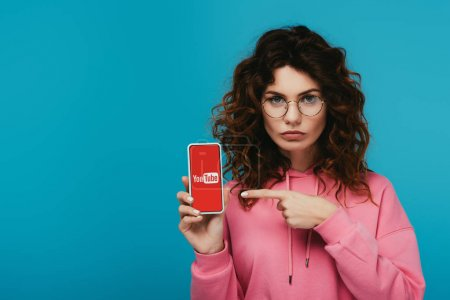 Photo for Attractive curly redhead girl pointing with finger at smartphone with youtube app on screen isolated on blue - Royalty Free Image