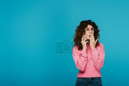 Photo for Surprised curly girl in glasses covering mouth while talking on smartphone on blue - Royalty Free Image
