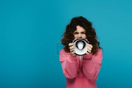 Photo pour Fille bouclée de rousse couvrant le visage avec le mégaphone tout en criant sur le bleu - image libre de droit