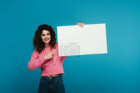 Photo pour Joyeuse rousse bouclée femme pointant du doigt la pancarte vierge sur bleu - image libre de droit
