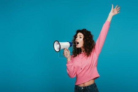 Foto de Atractiva chica pelirroja rizada gritando en megáfono en azul - Imagen libre de derechos