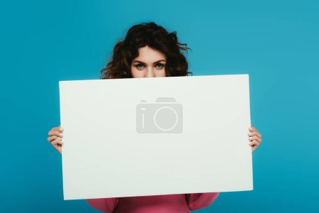 curly redhead woman covering face with blank placard on blue
