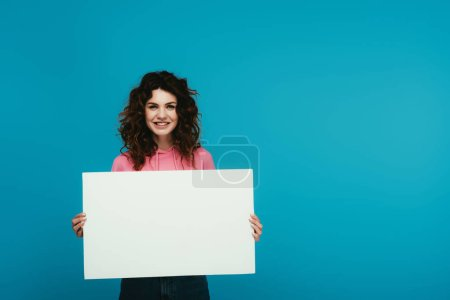 Photo pour Happy curly redhead woman holding blank placard on blue - image libre de droit