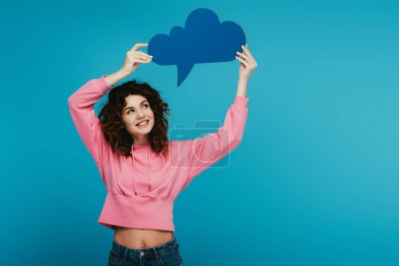 Photo for Happy curly redhead girl holding thought bubble on blue - Royalty Free Image