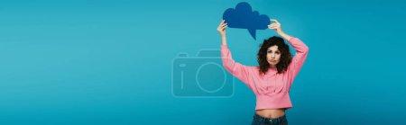 Photo pour Tir panoramique de la fille rousse bouclée bouleversée retenant la bulle de pensée sur le bleu - image libre de droit