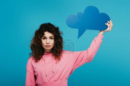 Photo pour Bouleversé rousse bouclée fille tenant bulle pensée sur bleu - image libre de droit