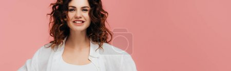 Photo for Panoramic shot of happy curly girl looking at camera and smiling isolated on pink - Royalty Free Image