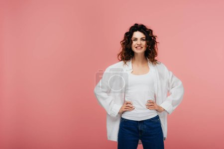 Photo for Happy young woman standing with hands on hips and smiling on pink - Royalty Free Image