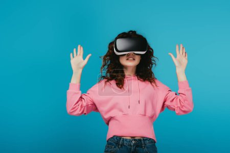 Photo for Curly woman wearing virtual reality headset and gesturing on blue - Royalty Free Image