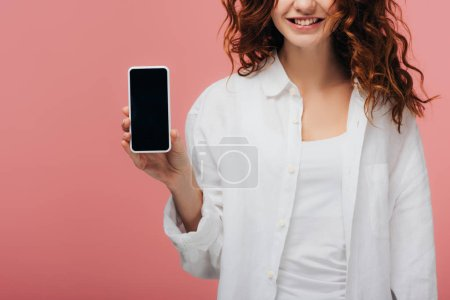 cropped view of cheerful girl holding smartphone with blank screen on pink