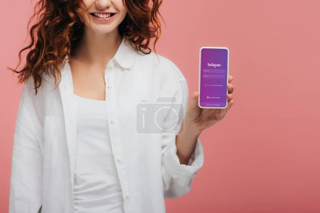 Photo for Cropped view of cheerful girl holding smartphone with instagram app on screen on pink - Royalty Free Image