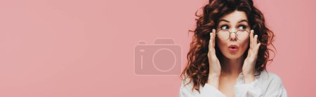 Photo for Panoramic shot of surprised curly girl touching glasses isolated on pink - Royalty Free Image