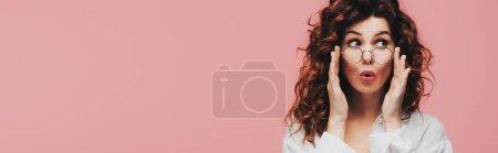 Photo pour Plan panoramique de surprise fille bouclée touchant des lunettes isolées sur rose - image libre de droit