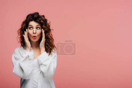 Photo pour Surprise fille bouclée avec des lunettes de contact cheveux rouges sur rose - image libre de droit