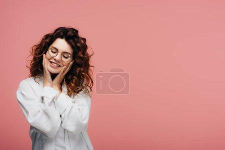 Photo pour Heureuse femme bouclée dans des lunettes souriant tout en touchant le visage sur rose - image libre de droit