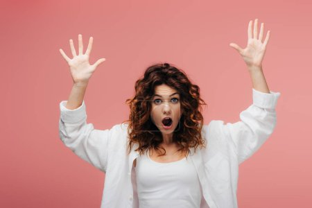 Photo for Shocked curly woman with red hair gesturing on pink - Royalty Free Image