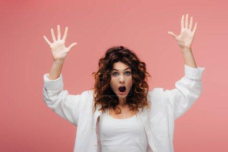 Foto de Shocked curly woman with red hair gesturing on pink - Imagen libre de derechos