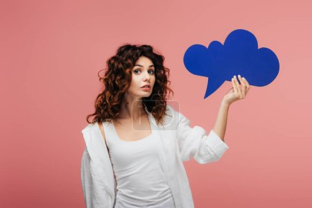 Photo for Attractive curly girl with red hair holding blue thought bubble on pink - Royalty Free Image