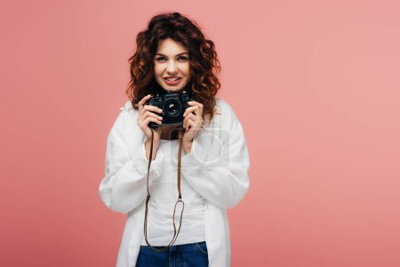 Photo for Cheerful young curly woman holding digital camera and smiling on pink - Royalty Free Image