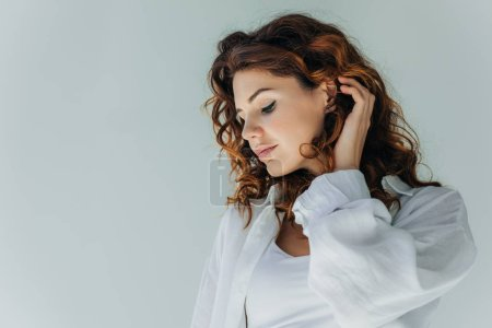 Photo for Attractive curly young woman touching hair on grey - Royalty Free Image