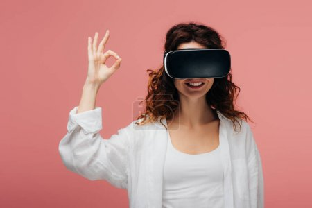 Photo for Happy curly redhead woman wearing virtual reality headset and showing ok sign on pink - Royalty Free Image
