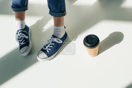 Photo for Cropped view of woman in sneakers near paper cup on white - Royalty Free Image