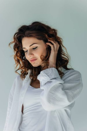 Photo for Happy curly young woman touching hair on grey - Royalty Free Image