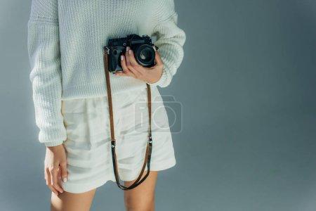 Photo pour Vue recadrée de la jeune femme tenant un appareil photo numérique sur gris - image libre de droit