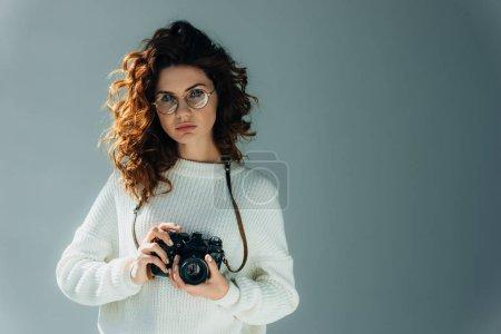Photo pour Jeune femme attirante avec le cheveu rouge retenant l'appareil-photo numérique sur le gris - image libre de droit