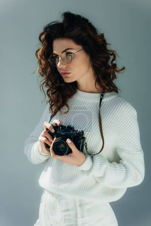 Photo for Beautiful young woman with red hair holding digital camera on grey - Royalty Free Image