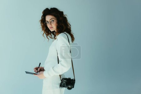 Foto de Attractive young woman with red hair holding notebook and pen while standing with digital camera on grey - Imagen libre de derechos