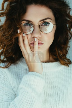 Photo pour Jeune femme attirante avec le visage touchant de cheveux roux et regardant l'appareil-photo sur le gris - image libre de droit