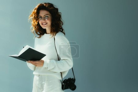 Photo for Happy young woman with red hair holding notebook and pen while standing with digital camera on grey - Royalty Free Image