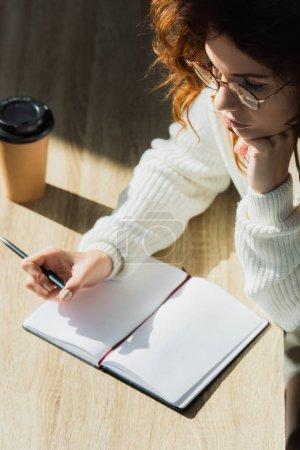 Photo pour Vue aérienne de la femme pensive de rousse dans des glaces retenant le stylo près du cahier vide - image libre de droit