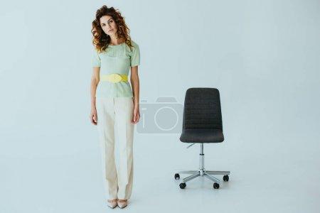 Foto de Atractiva pelirroja joven mirando a la cámara mientras está de pie cerca de la silla de oficina negro en gris - Imagen libre de derechos