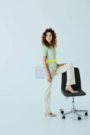 Photo for Attractive redhead young woman standing near black office chair on grey - Royalty Free Image