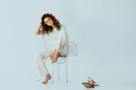 Photo pour Rousse bouclée jeune femme en lunettes de soleil jaunes regardant la caméra tout en étant assis sur la chaise près des talons sur gris - image libre de droit