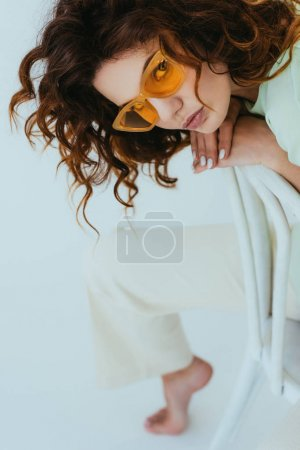 Photo for Overhead view of curly redhead young woman in yellow sunglasses looking at camera on grey - Royalty Free Image