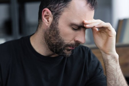Photo for Sad handsome bearded man with closed eyes holding hand near forehead - Royalty Free Image