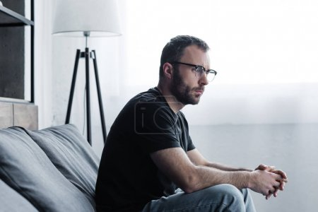 Photo for Thoughtful handsome man in glasses sitting on grey sofa and looking away - Royalty Free Image