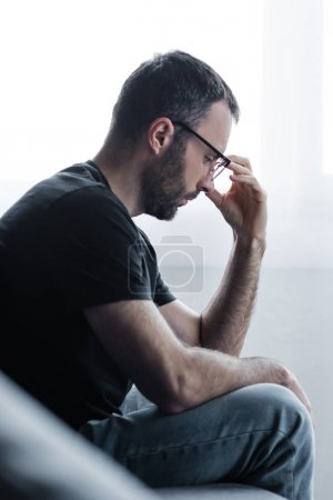 selective focus of sad bearded man in glasses holding hand near face