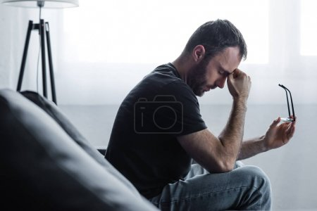 Photo for Upset man sitting on sofa with closed eyes and holding glasses - Royalty Free Image