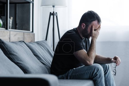 Photo for Depressed man holding glasses while sitting on sofa and covering face with hand - Royalty Free Image