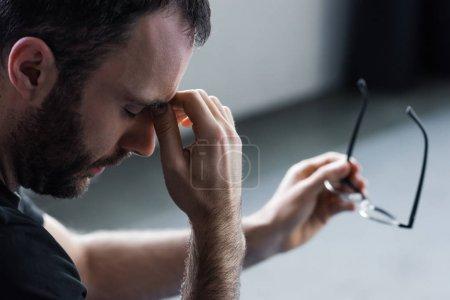 Photo pour Foyer sélectif de l'homme déprimé beau avec les yeux fermés retenant des glaces - image libre de droit