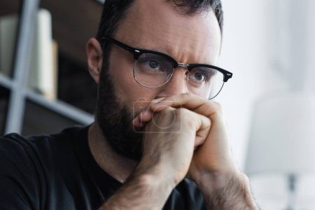 handsome depressed man in glasses holding folded hands near face