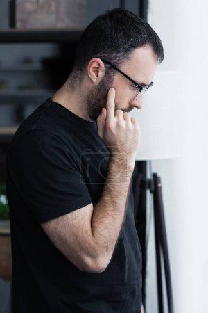 Photo pour Vue latérale de l'homme bouleversé dans le t-shirt noir et les glaces retenant la main près du visage - image libre de droit