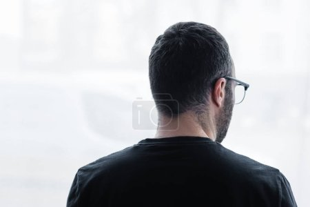 Photo for Back view of adult depressive man in black t-shirt looking out window at home - Royalty Free Image