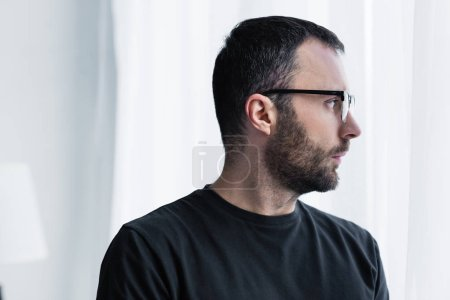Photo for Handsome pensive man in glasses looking out window at home - Royalty Free Image